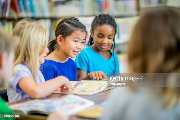 girls reading in a group - school child stock pictures, royalty-free photos & images