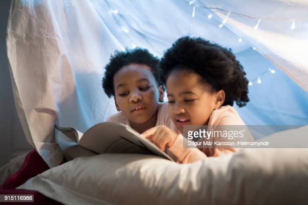 Girls reading story book while lying on bed