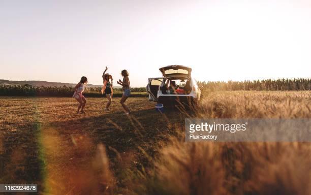 niñas relajándose en un campo agrícola - ancho fotografías e imágenes de stock