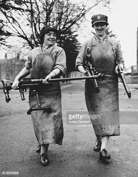 Girls return to an armoury with guns after cleaning them.