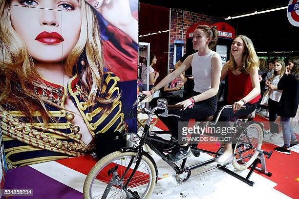 Girls ride a tandem during the Get Beauty fair a beauty and fashion fair inspired by the US 'Beautycon' event gathering of fashion bloggers and...