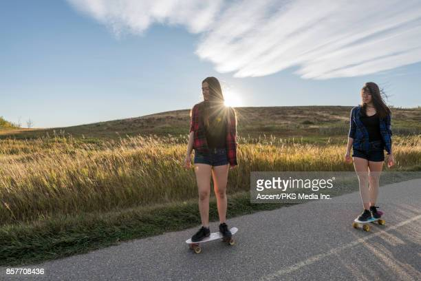 Girls ride skateboards along paved path through hills