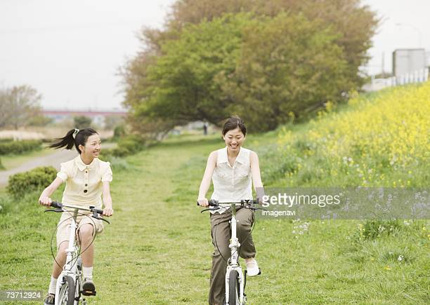 Girls riding bicycles in the frower field