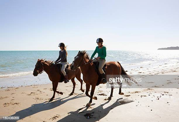 Girls riding horses on beach
