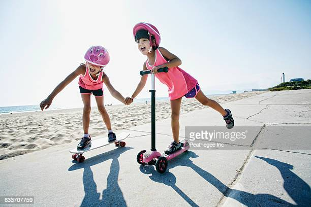 Girls riding skateboard and scooter at beach