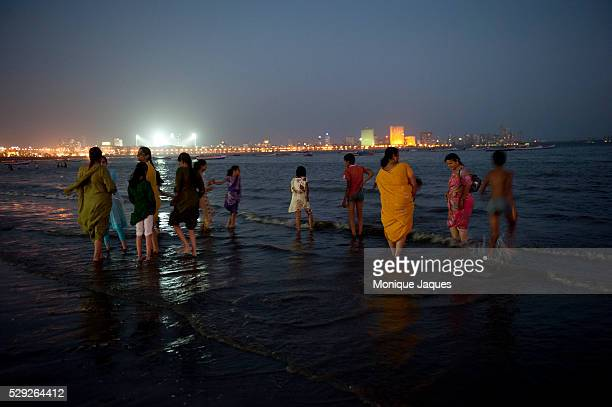 Girls run on the beach after the sun has set in Mumbai. Locals and tourists visit Chaowpatty Beach in Mumbai. Traditionally the site of the yearly...