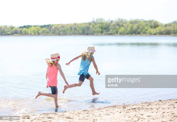 girls running along shoreline on beach - lake auburn stock photos and pictures