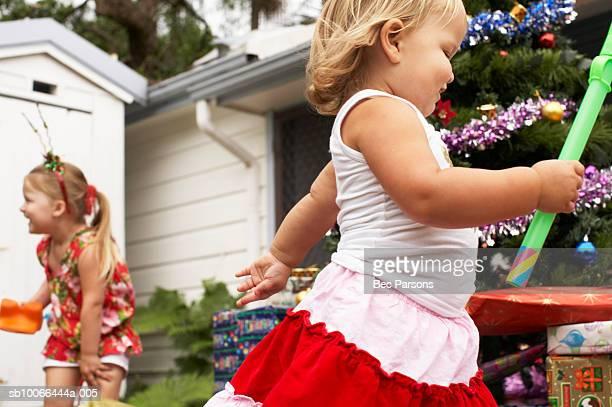 Girls (1-3) running around Christmas tree outdoors