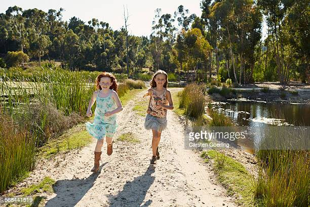 2 Girls running at a lake