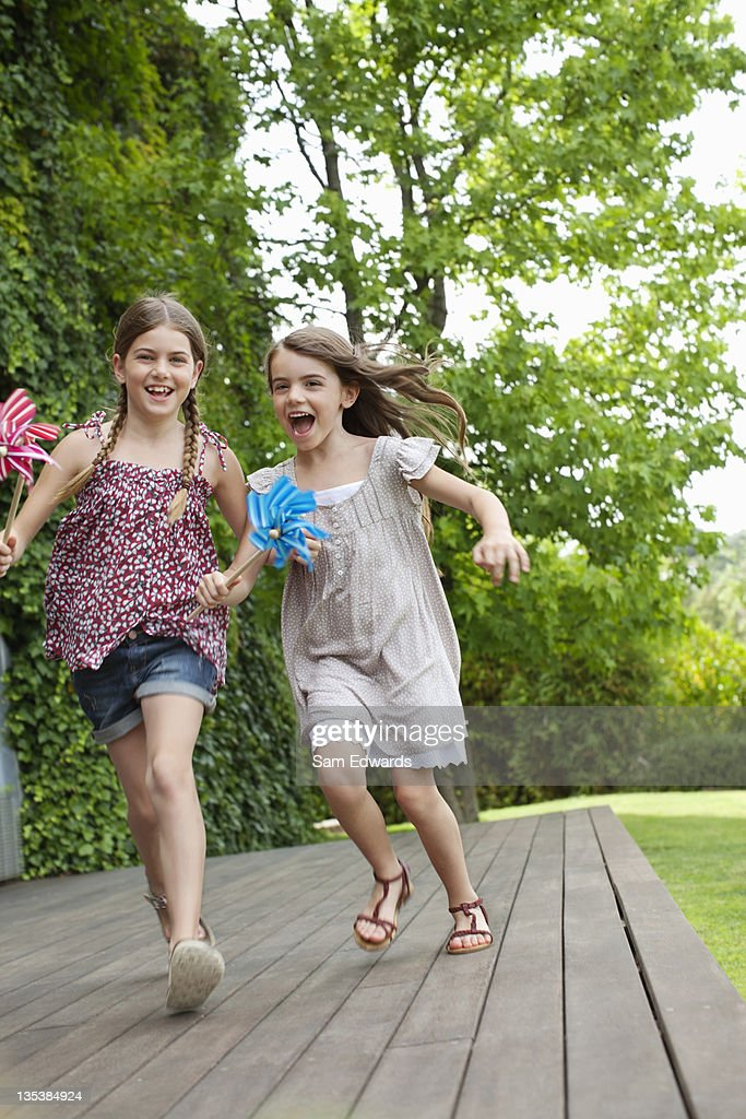 Girls running holding pinwheels : Stock Photo