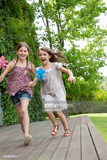 Girls running holding pinwheels
