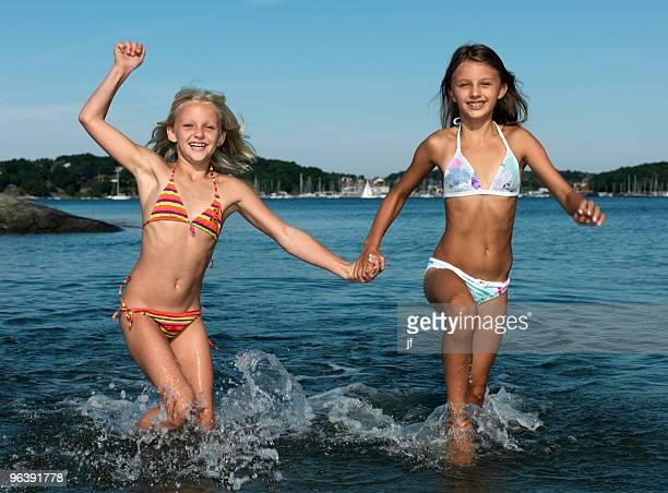 girls running in water - solo bambine femmine costume da bagno foto e immagini stock