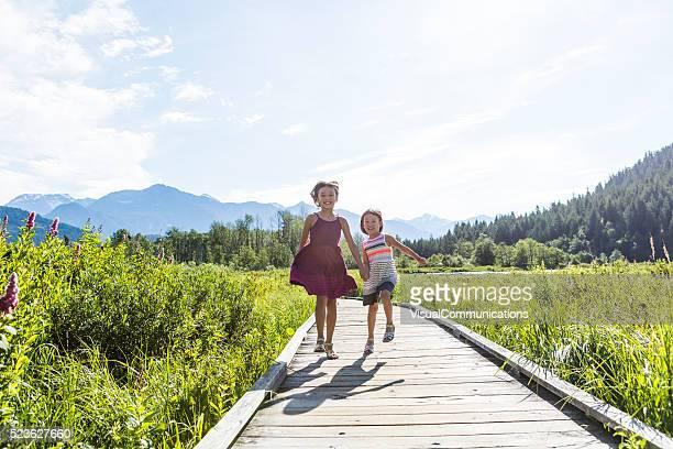 Girls running on boardwalk through lush greens.