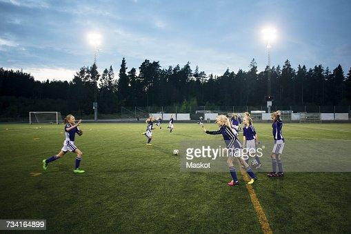Girls running on soccer field against sky