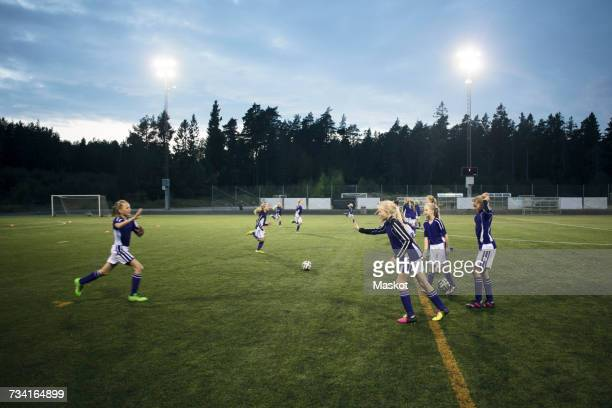 Girls running on soccer field against sky