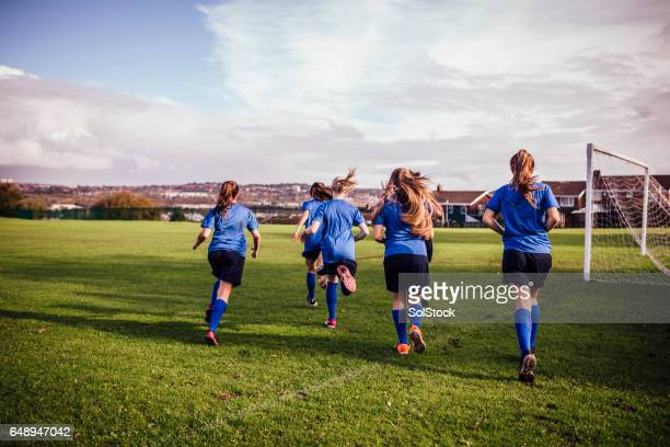 girls running onto a soccer playing field - rugby team stock pictures, royalty-free photos & images