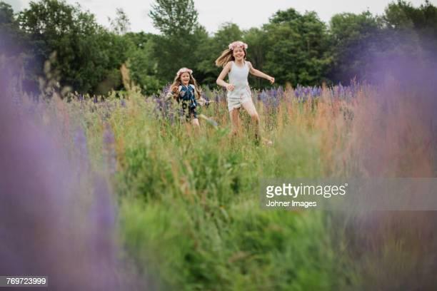 Girls running through meadow