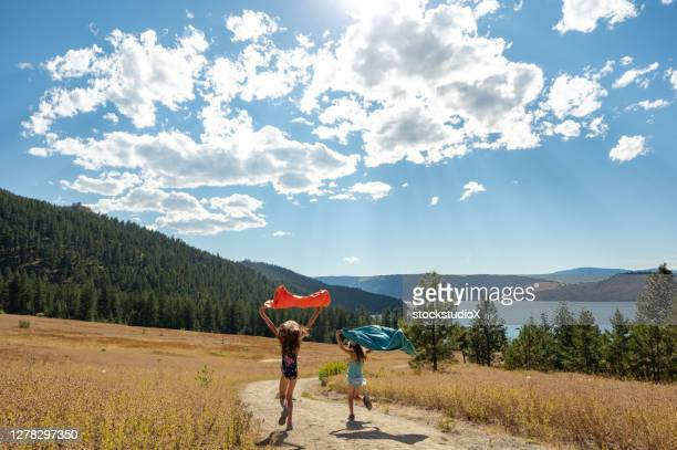 girls running to the beach with their towels - okanagan valley stock pictures, royalty-free photos & images