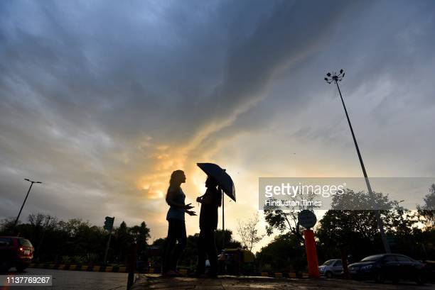 Girls seen with an umbrella during sudden rain at Mandi House on April 17 2019 in New Delhi India Strong winds accompanied by light rain lashed the...
