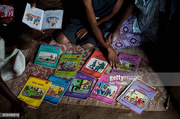 Girls select educational books at an adolescent youth center in Uganda The girls are offered critical life skills training to help them manage socail...
