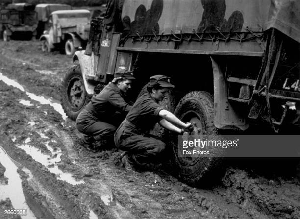 Girls service a six wheel truck at an RECCE Depot, prior to its departure for the Second Front.