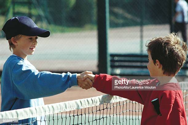 girls shaking hands at net on tennis court - respekt stock-fotos und bilder