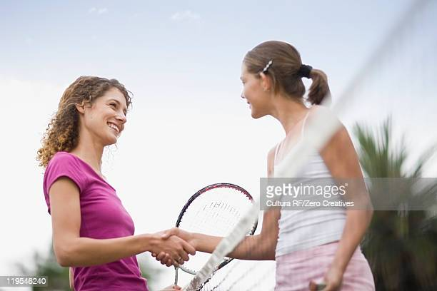 Girls shaking hands on tennis court