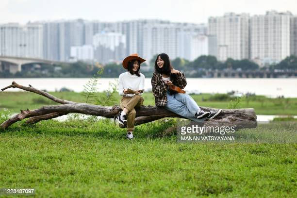 Girls share a light moment while posing for photographs at an open field along the banks of the Red river in Hanoi on September 13,2020.