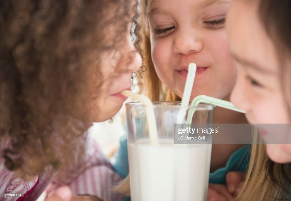 Girls sharing glass of milk : Stock Photo