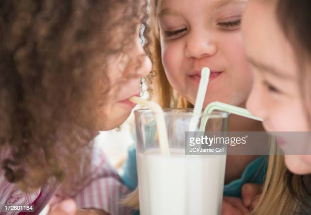 Girls sharing glass of milk