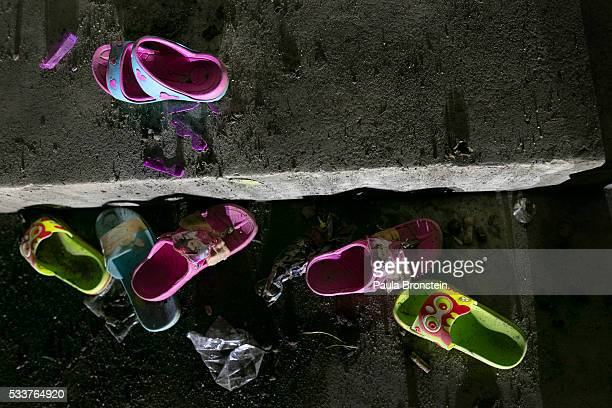 Girls Shoes are seen outside of the school dormitory where a fire broke out on Sunday night killing at least 17 girls in Wiang Papao Chiang Rai...