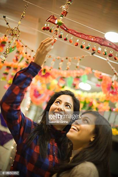 girls shopping wall hanging at a decorated shop in festival. - diwali celebration stock photos and pictures