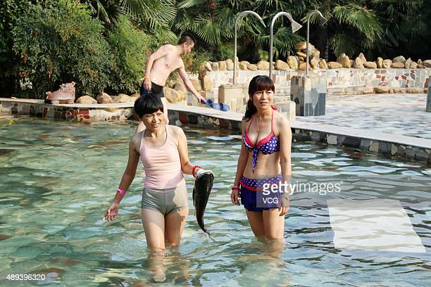 Girls show a fish in the hot spring during a competition on September 20 2015 in Zhengzhou Henan Province of China People who caught and held the...
