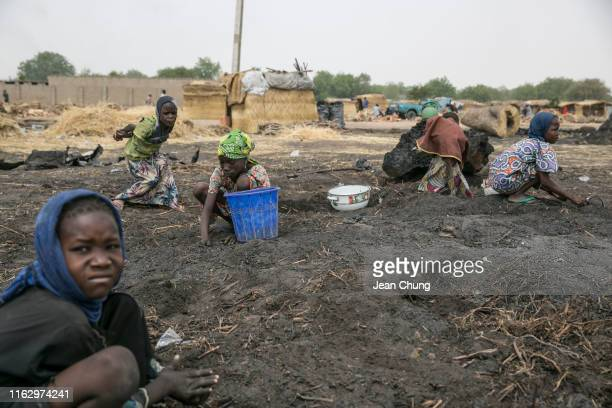 Girls sift through the ashes of charcoals inside an IDP camp on April 21 2019 in Maiduguri Nigeria General elections were held in Nigeria on 23...