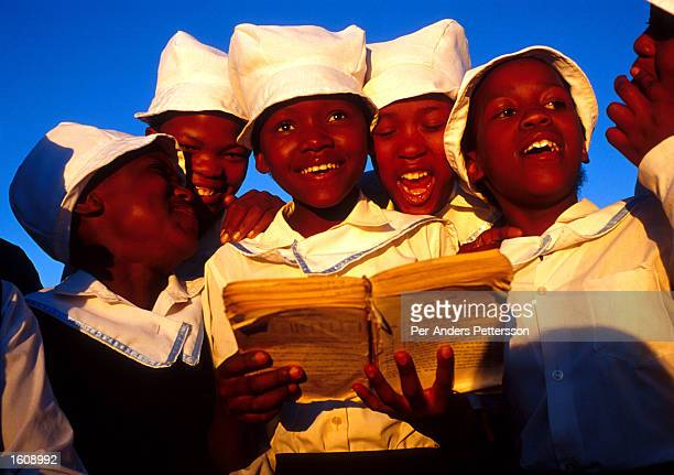 Girls sing a gospel song in a township June 19 2001 after going to church in Vryburg South Africa Vryburg a small and very conservative farming town...
