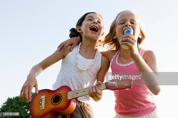 girls singing together outdoors - plucking an instrument stock pictures, royalty-free photos & images
