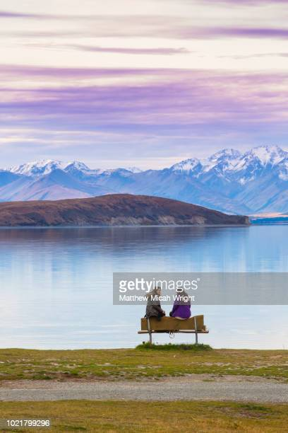 girls sit lakeside to admire the view of lake tekapo as a beautiful sunset descends over the lake and the snowcapped mountains. - matthew hale stock pictures, royalty-free photos & images