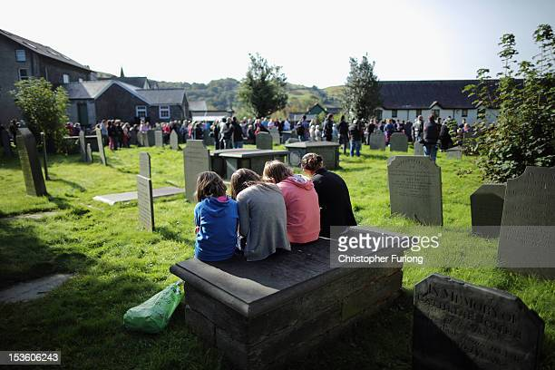 Girls sit on a tomb as other members of the community of Machynlleth stand in the church yard of St Peter's Church for a service with prayers for...