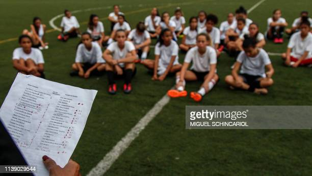 Girls sit on the pitch during a slection test to be part of the Sao Paulo FC under-15 female football team in Sao Paulo, Brazil, on April 22, 2019. -...