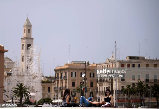 Girls sit on the seafront of Bari on May 12 2017 / AFP PHOTO / FILIPPO MONTEFORTE
