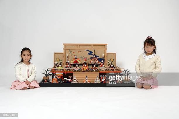 Girls sitting besides of hinamatsuri dolls