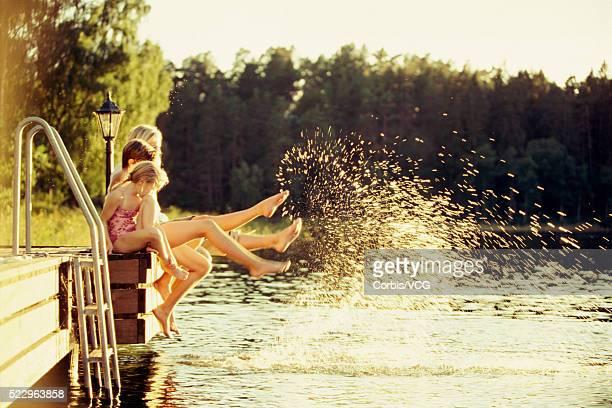 Girls Sitting By Lake and Splashing