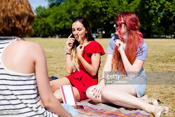 girls sitting down on grass enjoying the sun - only young women stock pictures, royalty-free photos & images