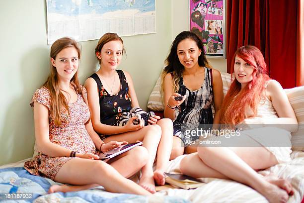 girls sitting down watching television together - only young women stock pictures, royalty-free photos & images