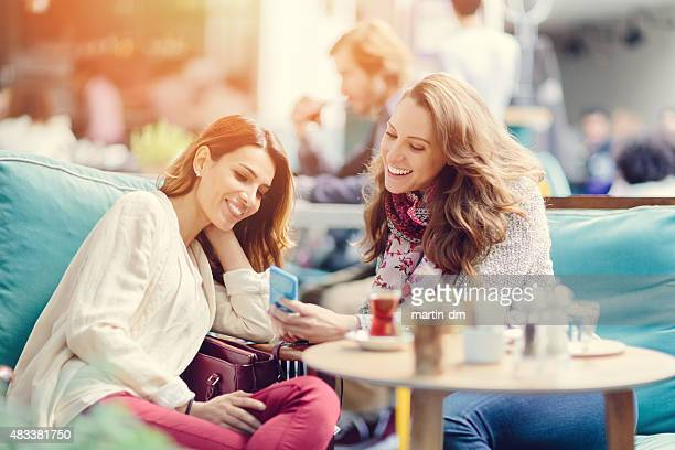 Girls sitting in a cafe and texting on smartphone