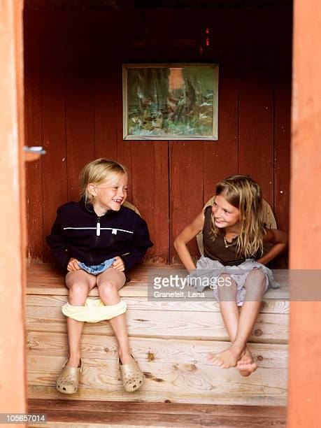 Girls sitting in outhouse