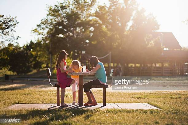 3 girls sitting in park painting - only girls stock pictures, royalty-free photos & images