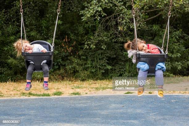 girls sitting in still swings - day 4 stockfoto's en -beelden