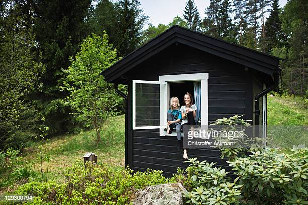 girls sitting in window of shack - non urban scene stock pictures, royalty-free photos & images