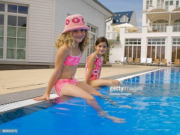 Girls sitting near pool